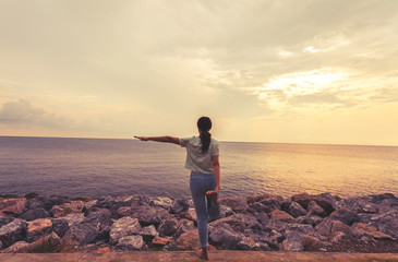A woman practices yoga on a background of sea and sky with silhouette background,dark tone and soft focus,processed in vintage style.