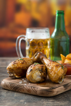 Roast chicken drumsticks, chips and beer on wooden table