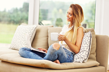 Woman on couch with laptop in living room