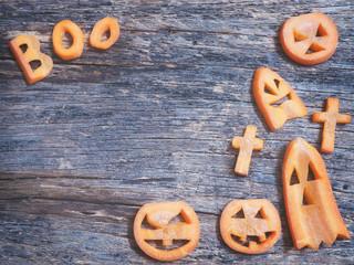 Halloween background.Scarved jack-o-lantern and spooky carrots on wooden background, vintage filter effect