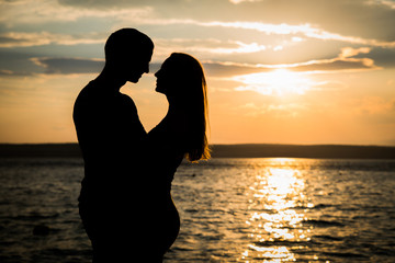 Couple in love silhouette shadow, holding, kissing - seaside, ocean, water, sunset, sunrise background. Dating, romantic, vacation, valentine's concept.
