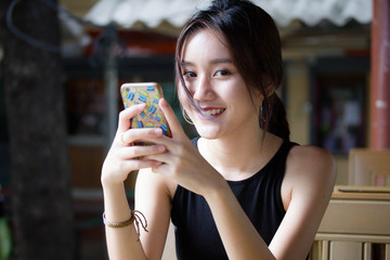 Portrait of thai adult student university beautiful girl using her smart phone