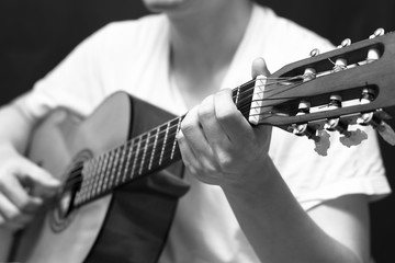 male musician playing classical, acoustic guitar.  filter