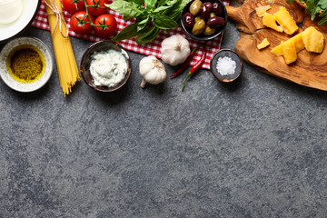 Italian food ingredients background with raw spaghetti, olives, basil leaves, parmesan cheese, mozzarella, ricotta, garlic, chili pepper, olive oil and tomatoes.