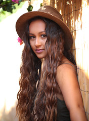 Pretty girl with long hair against a bamboo fence