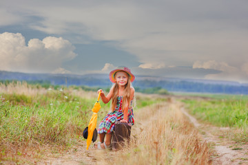 cute little girl in a hat sitting on a retro suitcase in the field. in the hands holding an umbrella. soon it starts to rain.