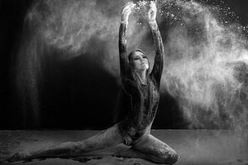Young woman dancing in flour cloud