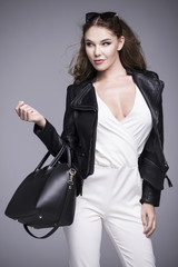 A beautiful woman in a white dress and black leather jacket