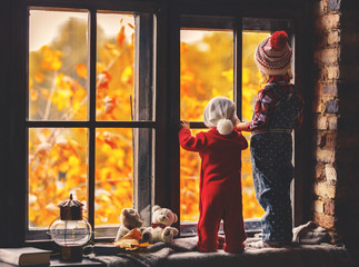 happy children brother and sister looking through windows in fal