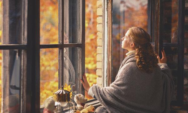 happy young woman enjoying fresh autumn air at open window
