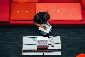 Woman at red sofa with laptop, high angle view
