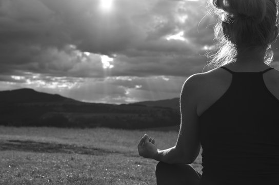 Grayscale image of a lady who is meditating on a field faced to the sun behind stormy sky on west in late afternoon