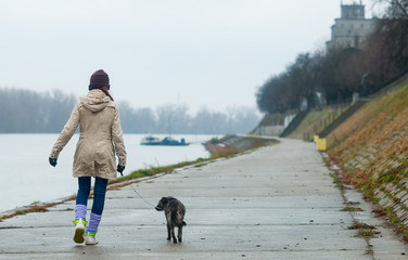 Teenage girl walking dog on cloudy autumn day.