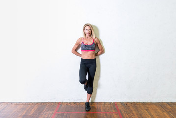 Woman standing against a wall in a gym