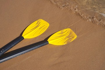 Yellow oars on sandy beach with motion blur from waves