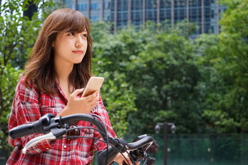 Young Japanese woman using smartphone (cell phone) riding on a bike in a city
