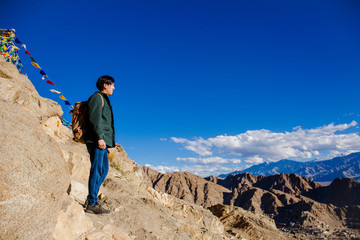 Young Asian traveler standing on high hills and looking away at the village over blue sky background in Leh, Ladakh, India