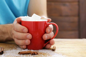 man holding a mug hot cocoa with marshmallows, winter Christmas drink