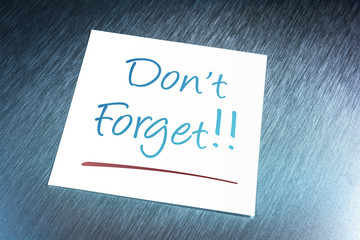 Don't Forget Reminder On Paper Lying On Brushed Aluminum