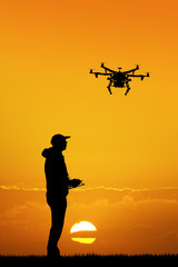 man with drone at sunset