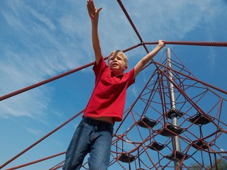 Boy on pyramid net climber under blue sky with white clouds