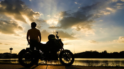 Silhouette biker with his motorbike beside the natural lake and beautiful sunset sky.