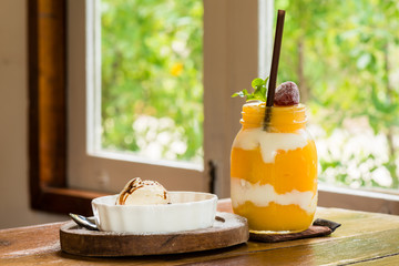 grass of mango smoothie and ice cream on wooden table