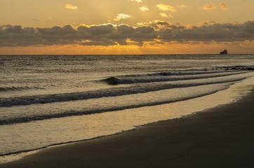 Sea-going vessel near the coast at sunset.