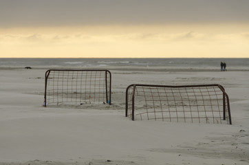 Soccer goals on a beach at sunset.