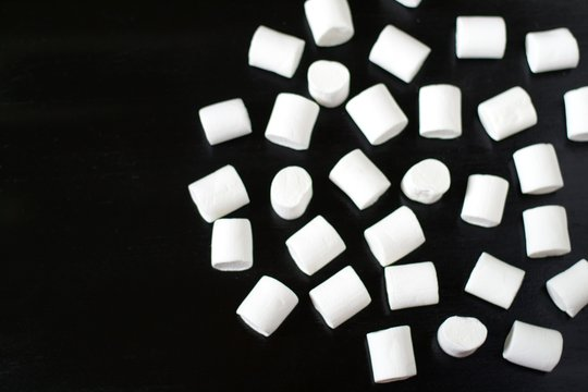 marshmallow on a dark background, blurred image, top view