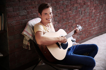 Young man playing guitar and sitting on chair in a room