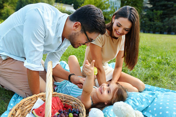 Family In Park. Happy Young Parents And Child Relaxing Outdoors