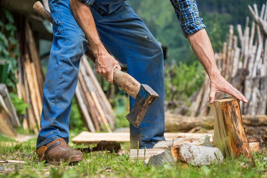 Male worker with axe wood chopping firewood