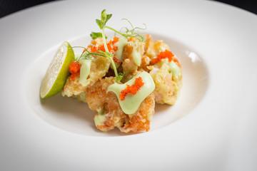 shrimp tempura with roe on white plate, restaurant