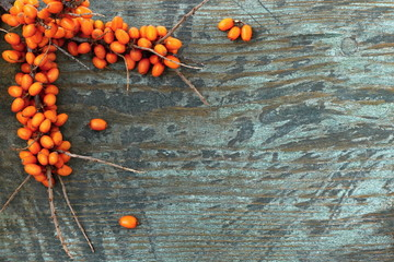 Sea buckthorn branch with orange berries on a wooden background. Autumn background with orange berry fruits on a wooden background. Top view.