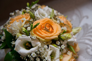 Two beautiful gold wedding rings lie on a saucer with flowers.