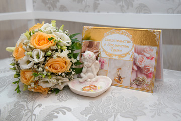 Two gold wedding rings lie on a platter in a rose shape with the angel sculpture near the bride's bouquet of orange roses and white flowers.