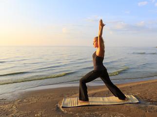 Fotobehang School de yoga Beautiful young woman practising yoga on mat outdoors at river bank on sand at sunset