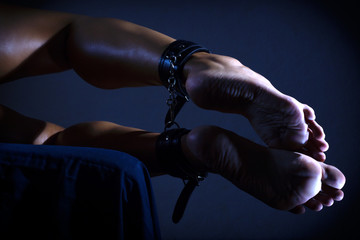 Low key photo of sexy female nude legs binded with cuffs against dark background