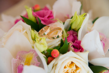 Two wedding gold rings with a diamond lying on the bride's bouquet of white orchids and pink flowers.