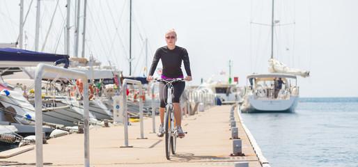 Young active woman cycling on pier in Rovinj marina, Istria, Croatia