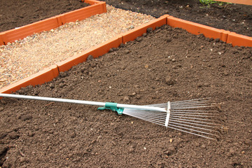 Soil alignment with a lawn rake on a modern plastic raised garden vegetable bed in the summer garden