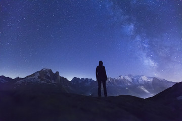 Person watching the stars above the Alps mountains range