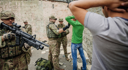 soldiers with weapon captured terrorists