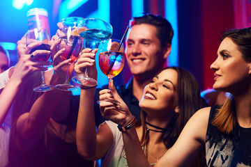 Portrait of joyful friends toasting at party in the club