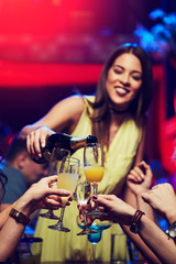 Smiling girl in the club poured champagne to her friends