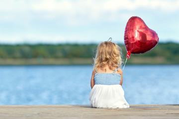 kleines Mädchen sitzt am Steg mit roten Ballon