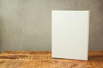 White canvas on wooden table over rustic background. Mock up template