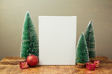 Christmas holiday mock up with canvas and pine tree on wooden table