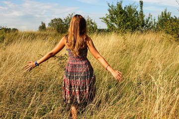 Young beautiful girl walking in the field and runs hand through the high dry grass at summertime.